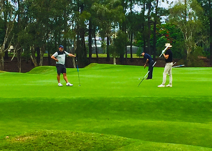 3 golfers putting